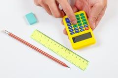 Les mains calculent utilisant une calculatrice numérique au-dessus du lieu de travail de l'ingénieur images libres de droits