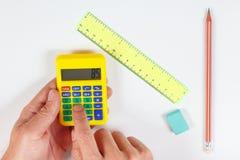 Les mains calculent utilisant une calculatrice numérique de poche au-dessus d'un lieu de travail d'ingénieur photo libre de droits