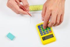 Les mains calculent utilisant une calculette au-dessus du lieu de travail de l'ingénieur photos stock