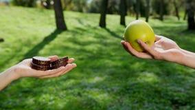Les mains choisissent ce qui mange une pomme verte ou le chocolat font cuire au four ? l'arri?re-plan il y a un parc, temps ensol banque de vidéos