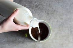 Les mains d'adolescente versent le lait images stock