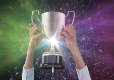 les mains d'affaires avec le trophée, le fond noir avec le rose et le vert évase Image stock