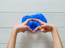 Les mains d'enfant montre le coeur de la boue plus de bleue photo stock
