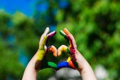 Les mains d'enfants peintes dans des couleurs lumineuses font une forme de coeur sur le fond de nature d'été Image stock
