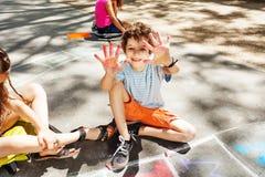 Les mains d'expositions de garçon colorées avec la craie fait le jeu de marelle Photo stock