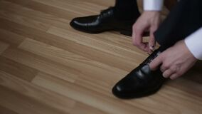 Les mains d'homme attachent les chaussures de mode de mariage Vue de plan rapproché banque de vidéos