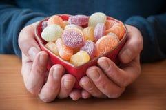 les mains d'homme avec les sucreries traditionnelles dans formé entendent Images stock