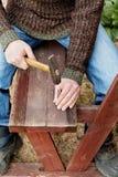 Les mains d'homme conduisent le clou avec un marteau dans le banc en bois Photos libres de droits