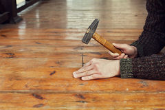 Les mains d'homme conduisent le clou avec un marteau dans le plancher en bois, menuiserie Image libre de droits