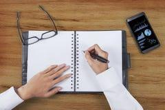 Les mains d'homme d'affaires rédigent le rapport de gestion Photos libres de droits