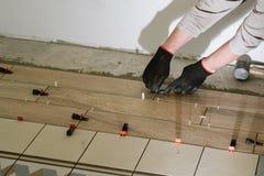 Les mains d'homme de maçon de construction sur des tuiles fonctionnent avec le mortier de ciment photographie stock libre de droits