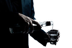 Les mains d'homme se ferment vers le haut de l'alcool blanc se renversant Photographie stock