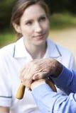 Les mains d'homme supérieur se reposant sur le bâton de marche avec le travailleur de soin dedans Image libre de droits