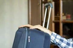Les mains d'homme tiennent une grande valise pour commencer le voyage f photo libre de droits