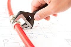 Les mains d'hommes avec la clé relient un tuyau Photo stock