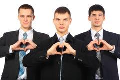 les mains d'hommes d'affaires aiment des jeunes du signe trois d'exposition Images libres de droits