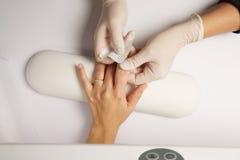 Les mains d'un docteur appliquant le bandage adhésif sur la femme caucasienne de genou ont isolé le fond blanc Photo libre de droits