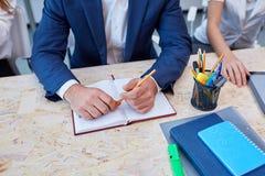 Les mains d'un homme dans un costume se repose au bureau et tient un crayon à côté d'un bloc-notes photos libres de droits