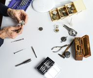Les mains d'un horloger réparant une montre mécanique photographie stock