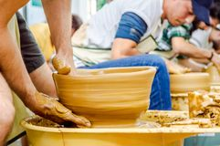 Les mains d'un jeune homme créant un argile cognent sur une roue de potier photo libre de droits
