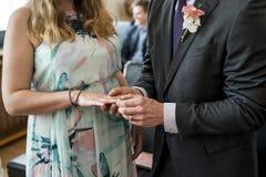 Les mains d'un marié de cérémonie de mariage de couples de mariage ont mis l'anneau sur le doigt de sa belle épouse Photos stock