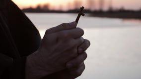Les mains d'un moine tenant une croix banque de vidéos