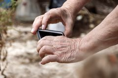Les mains d'une femme agée avec un téléphone portable Photos libres de droits