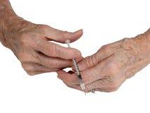 Les mains d'une femme d'aîné avec la seringue Photo libre de droits