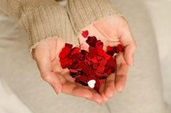 Les mains d'une jeune fille caucasienne tiennent de petits coeurs Images libres de droits