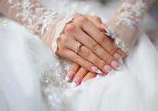 Les mains d'une jeune mariée avec un anneau et un mariage manicure Photos libres de droits