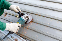 Les mains dans des gants de chiffon rectifie la structure métallique ondulée pour rouille de couche de fond l'anti Image stock
