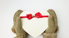 Les mains dans des mitaines beiges tiennent un boîte-cadeau sous forme de coeur avec un ruban rouge avec un arc sur un fond blanc photo libre de droits