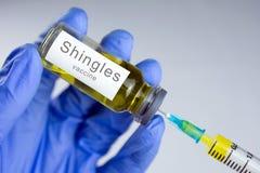 Les mains dans les gants bleus dactylographient un vaccin jaune dans une seringue photos stock