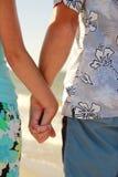 Les mains dans l'amour couplent tenir des mains sur le bord de mer Images stock