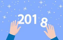 les mains de 2018 ans sont des nombres sur le fond bleu avec des flocons de neige Images libres de droits