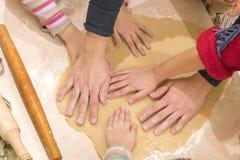 Les mains de bébé déroulent la pâte pour faire cuire les biscuits Le concept du travail d'équipe et de l'amitié images libres de droits