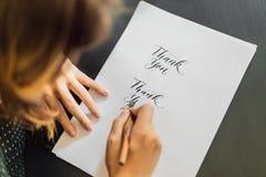 Les mains de calligraphe écrit l'expression sur le livre blanc Exprimez - merci Inscrire les lettres décorées ornementales image stock