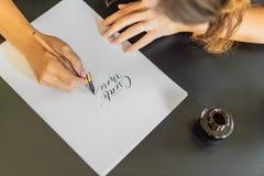 Les mains de calligraphe écrit l'expression sur le livre blanc Exprimez - pour créer plus Inscrire les lettres décorées ornementa image libre de droits