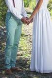 Les mains de chacun de prise de jeunes mariés sur une traînée de montagne Image stock