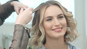 Les mains de coiffeur font les boucles smal, parlant avec un jeune modèle Photos stock