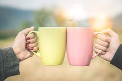 Les mains de couples font tinter la tasse de café chaude extérieure pendant le matin Photo stock