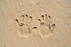 Les mains de couples impriment sur le sable avec des anneaux de mariage Photographie stock