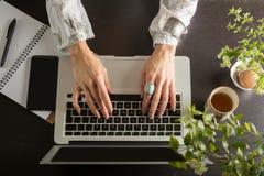 Les mains de femme écrivent sur l'ordinateur, vue d'en haut Image libre de droits
