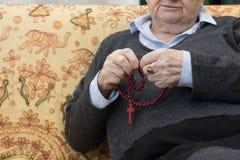 Les mains de femme agée se ferment vers le haut de la prière catholique religieuse avec le ROS Photos stock