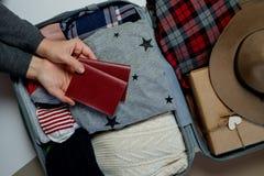 Les mains de femme avec des passeports sur le fond ouvrent le packe de valise image libre de droits