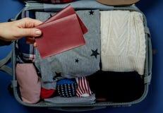 Les mains de femme avec des passeports sur le fond ouvrent le packe de valise images libres de droits