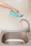 Les mains de femme avec la bouteille du détergent de nettoyage pour le métal descendent dans la cuisine Images libres de droits