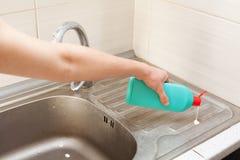 Les mains de femme avec la bouteille du détergent de nettoyage pour le métal descendent dans la cuisine Photo stock