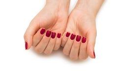Les mains de femme avec le clou rouge d'isolement sur le blanc Photos libres de droits