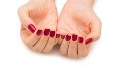 Les mains de femme avec le clou rouge d'isolement sur le blanc Photo stock